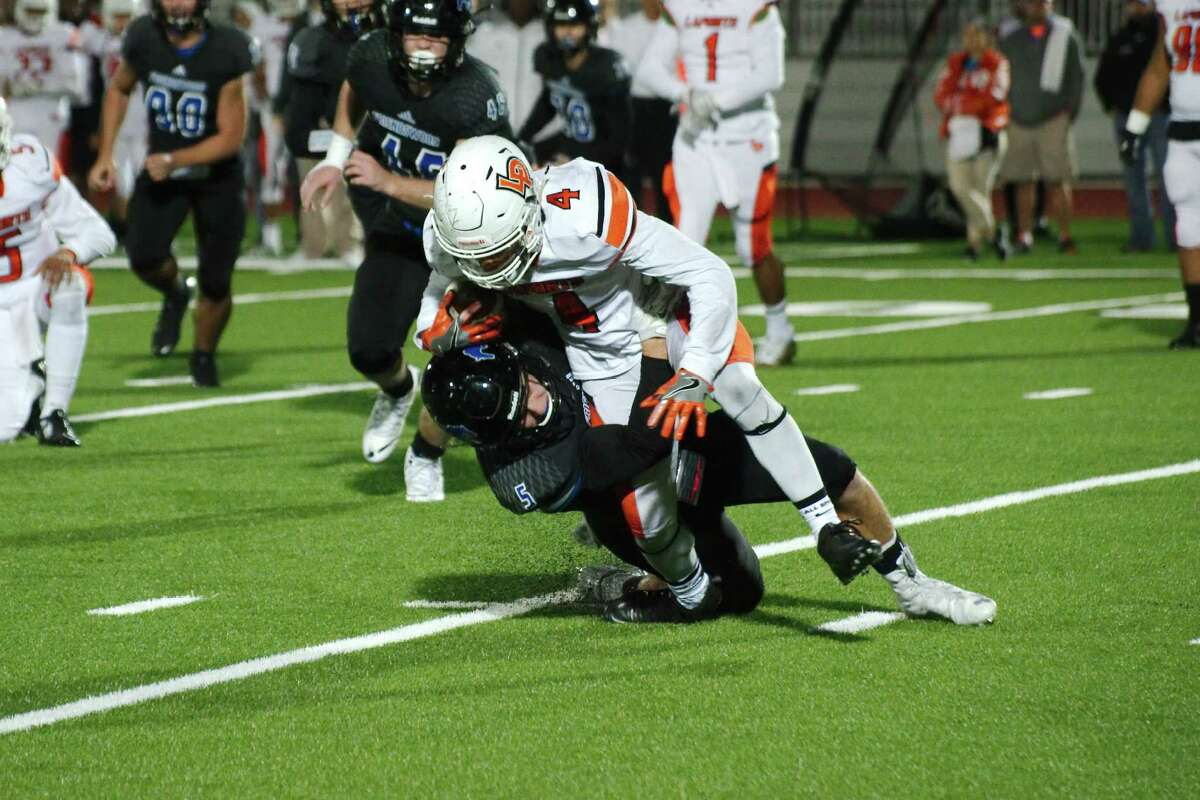 Friendswood defensive back Weston Owens (5) brings down La Porte running back Kevrin Busby Friday night at Challenger Columbia Stadium.