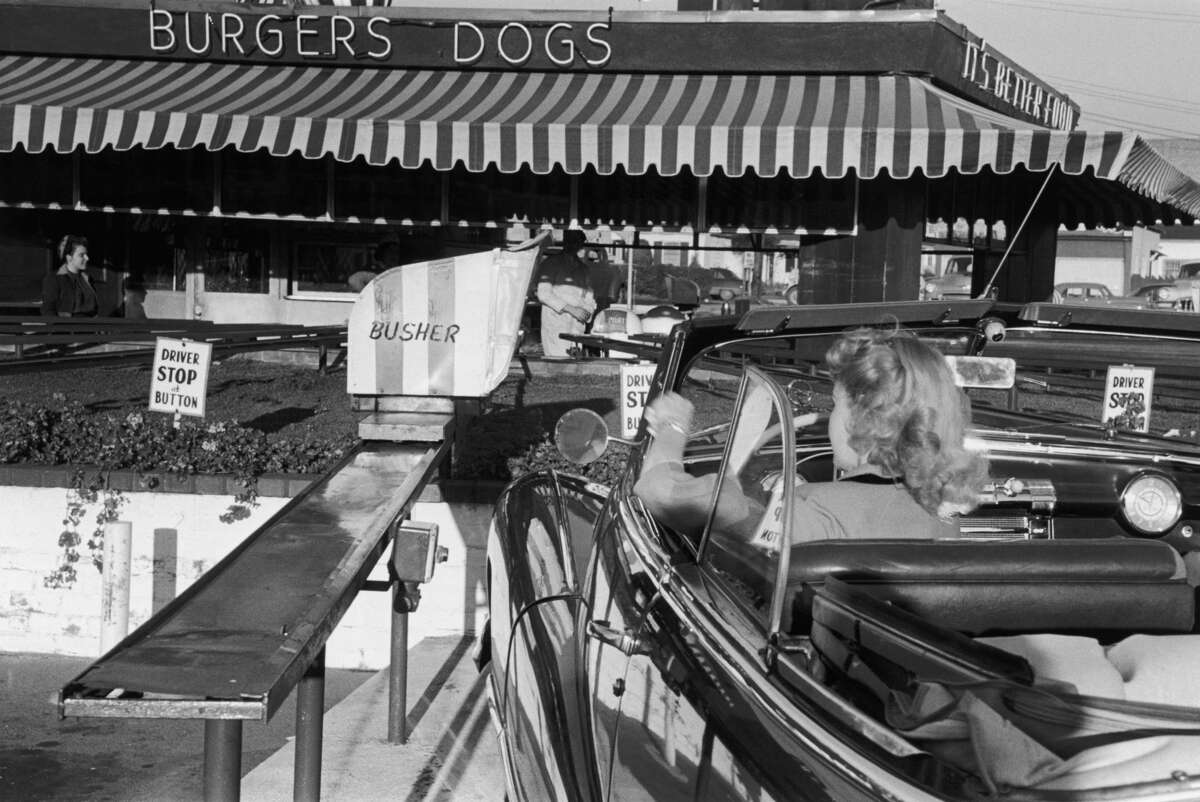 An American motorist stops at a drive-through burger joint in Hollywood, California. Original Publication: Picture Post - 5298 - We Go To Hollywood - pub. 1951 (Photo by Kurt Hutton/Getty Images)
