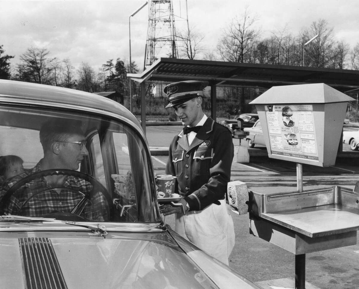 A uniformed carhop serves food to a drive-in customer at Tops Restaurant, 1959. (Photo by PhotoQuest/Getty Images)