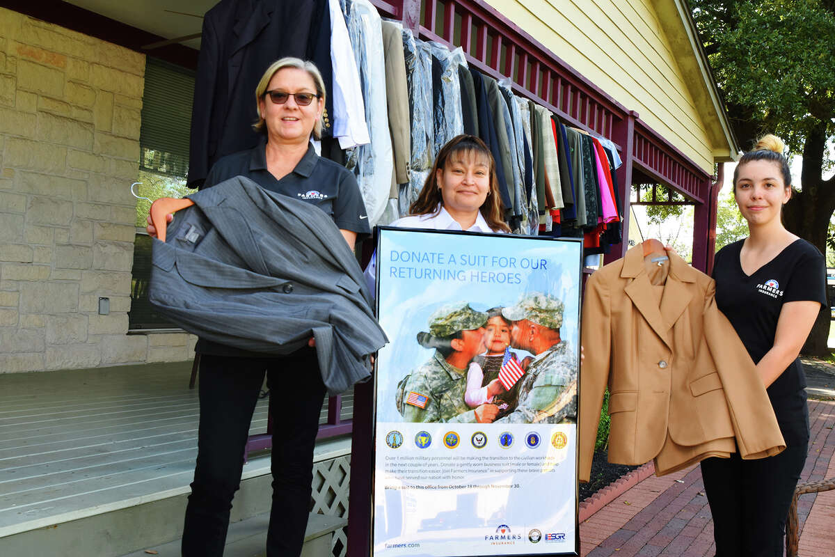 Tomball Mayor Gretchen Fagan, left, joins Terry Hitt and ChelseyEspitia to show some of the donated clothes for the military families.