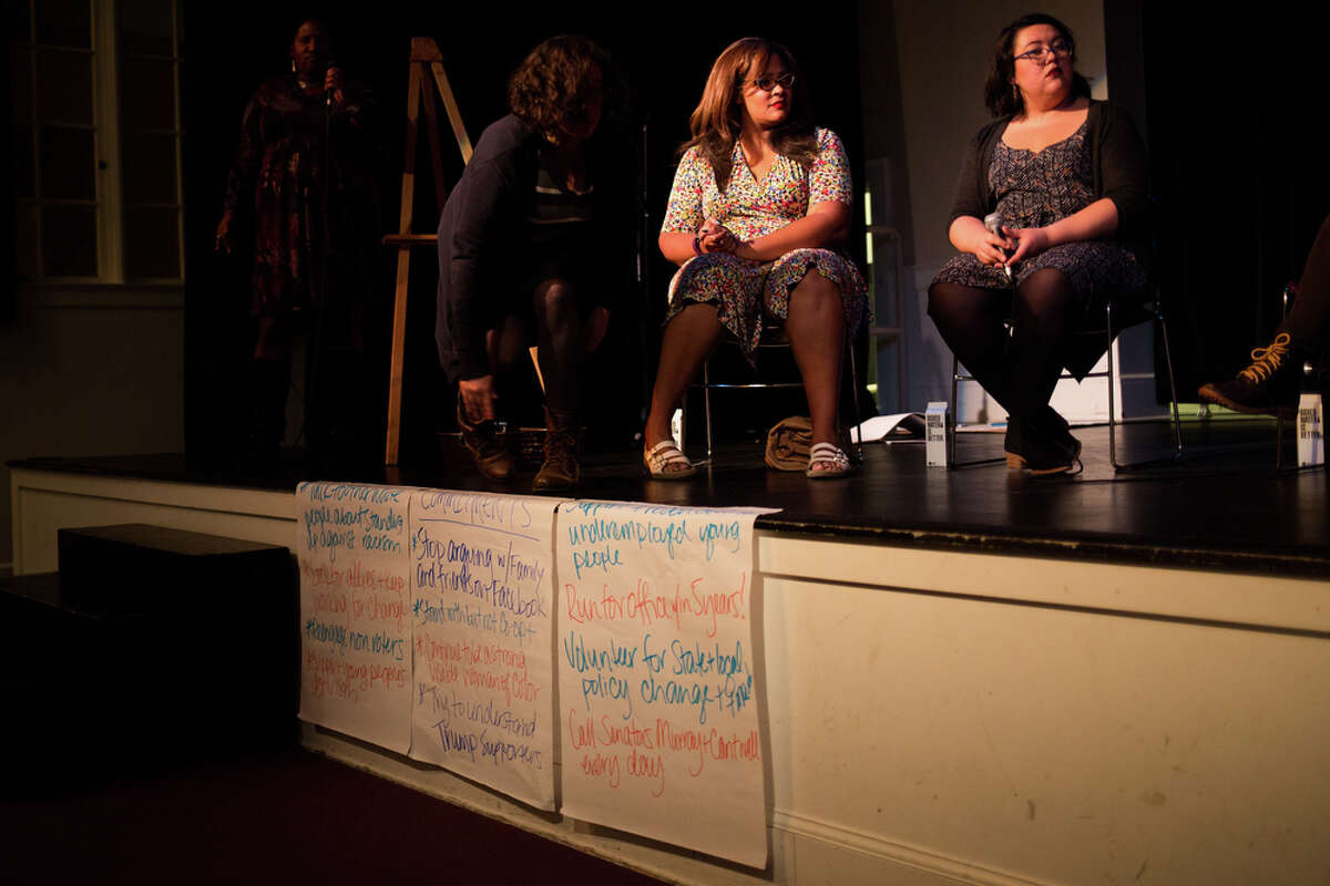 Ijeoma Oluo and Ana Sofia Knauf sit on a panel above a list of commitments the crowd made in the wake of the recent election of Donald Trump, at What We Must Do Now, an event held by South Seattle Emerald at Rainier Arts Center on Friday, Nov. 18, 2016.