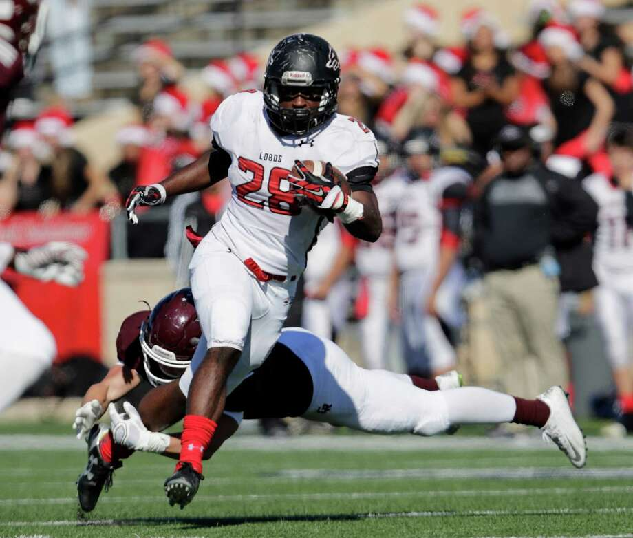 Langham Creek Lobos running back Toneil Carter (28) runs the ball past a diving Cinco Ranch Cougars defender during the high school playoff football game between the Langham Creek Lobos and the Cinco Ranch Cougars at Tully Stadium in Houston, TX on Saturday, November 19, 2016.    The Cougars lead the Lobos 17-14 at halftime. Photo: Tim Warner, For The Chronicle / Houston Chronicle