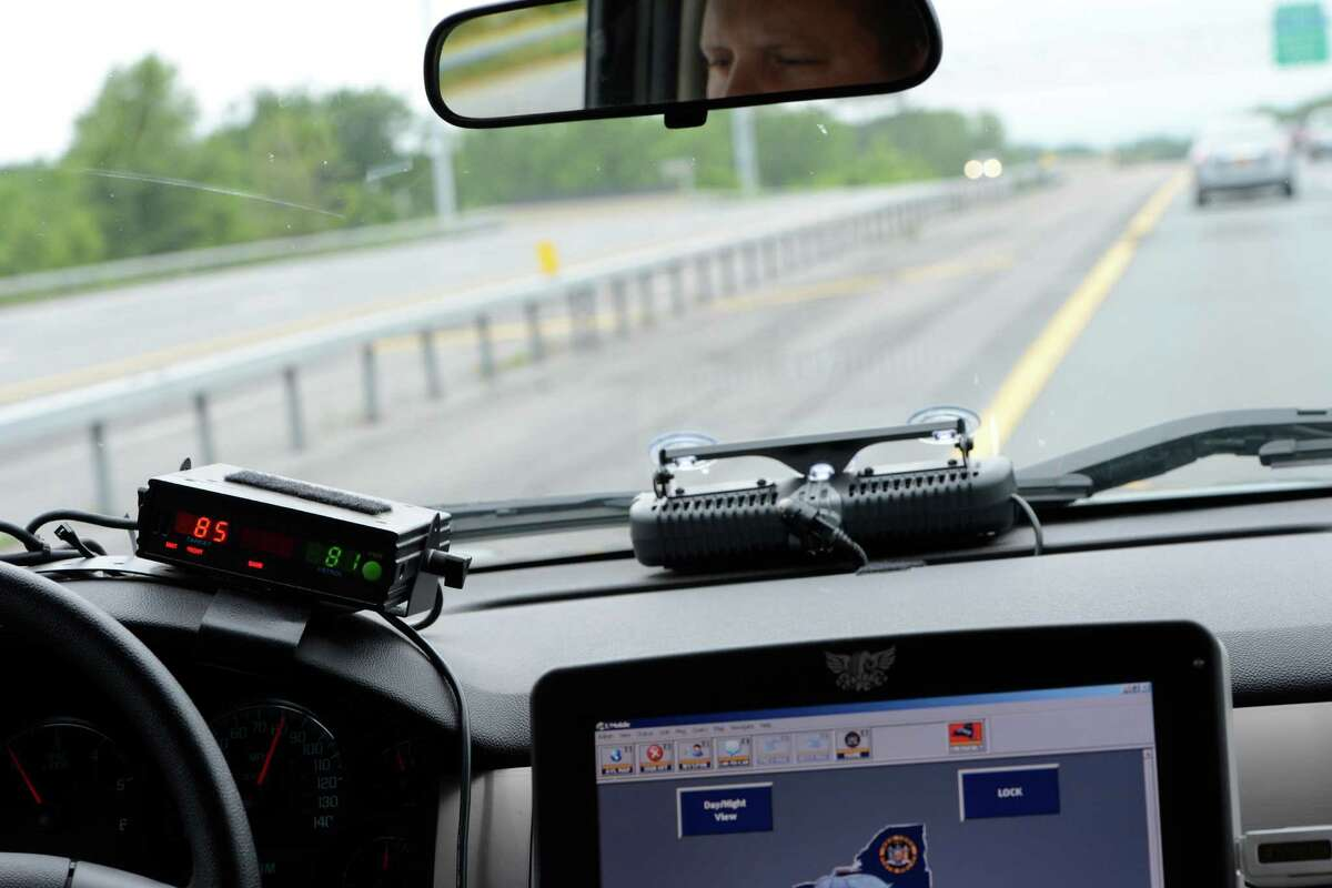 NYSP trooper Dan Borecki follows a car during a vehicle stop for speeding on I-87 on June 12, 2012, in Colonie, N.Y. The radar readout shows the cruiser speed in green and the speeders in red. (Skip Dickstein / Times Union archive)