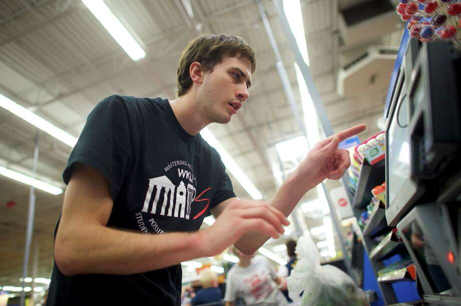 Crosby Gardner determines how to operate the self-checkout machine at Wal-Mart on a shopping trip with fellow students from Western Kentucky University's Kelly Autism Program in Bowling Green, Ky. Photo: MARK MAKELA, STR / NYTNS