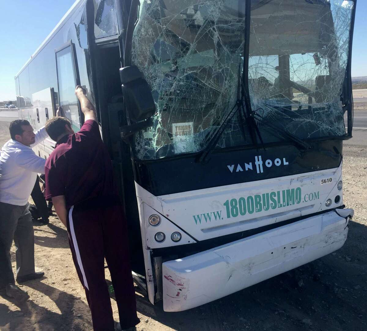 Texas State officials stand at the doorway to one of three charter busses damaged in Saturday's accident on the Texas and New Mexico border. Five people were transported to an area hospital. The busses, carrying the Texas State football team, cheerleaders and support staff was en route to a football game at New Mexico State.