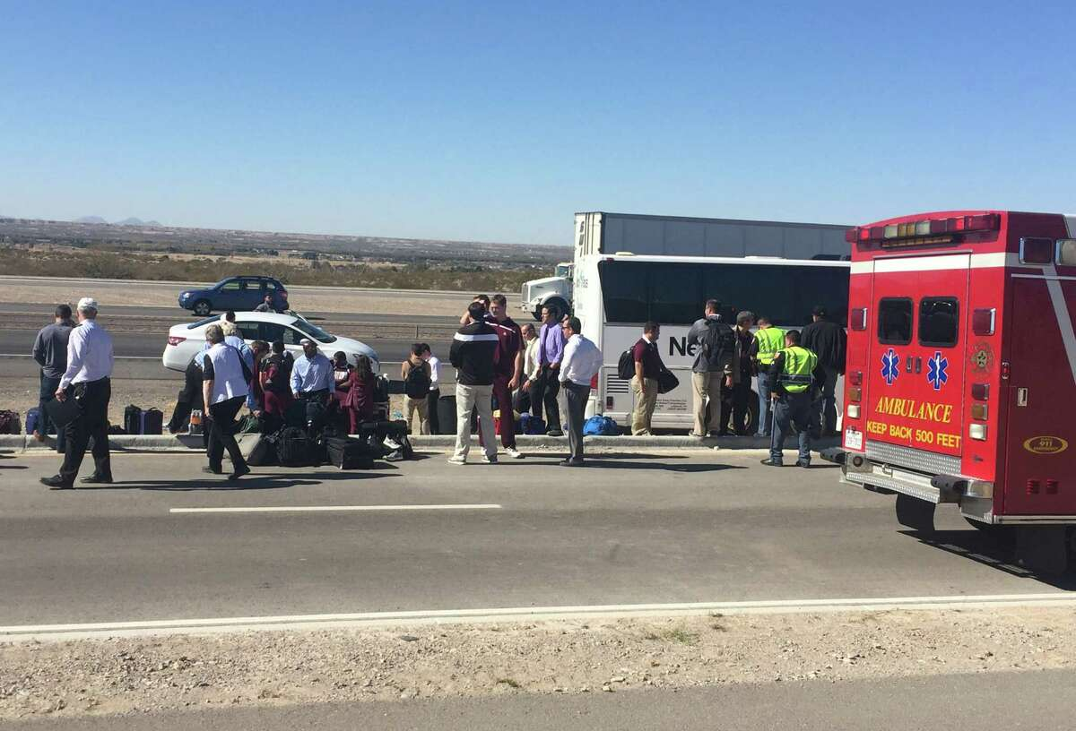 Texas State football team players and support staff stand outside one of three charter busses involved in an accident Saturday while on their way to a game against New Mexico State. Five people aboard the busses were transported to an area hospital with injuries.