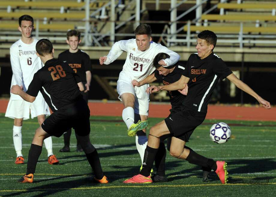 Farmington Kyle Gudewicz gets off a shot under pressure from Shelton Kelan Smith, Anthony Russo and Ethan Shuster in the CIAC Class LL boys soccer final at Memorial Stadium in New Britain on Nov. 19, 2016. Farmington defeated Shelton 3-0. Photo: Matthew Brown / Hearst Connecticut Media / Stamford Advocate