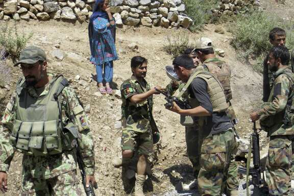 Soldiers with the Afghan National Army stopped to drink yogurt milk brought to them by a young girl while they were on patrol in September near the Pakistan border in eastern Afghanistan's Nangarhar province.
