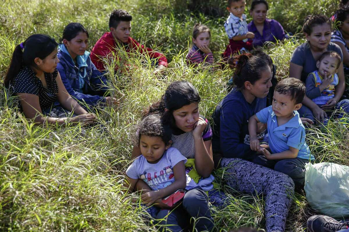 A group of immigrants sit next to a road after they crossed into the United States and were detained by Border Patrol Wednesday, Nov. 16, 2016 in McAllen. Most immigrants are arriving from El Salvador, Honduras and Guatemala where they are escaping violence and poverty. They hope to be found by border patrol to be processed, released and begin the process to stay in the country. ( Michael Ciaglo / Houston Chronicle )