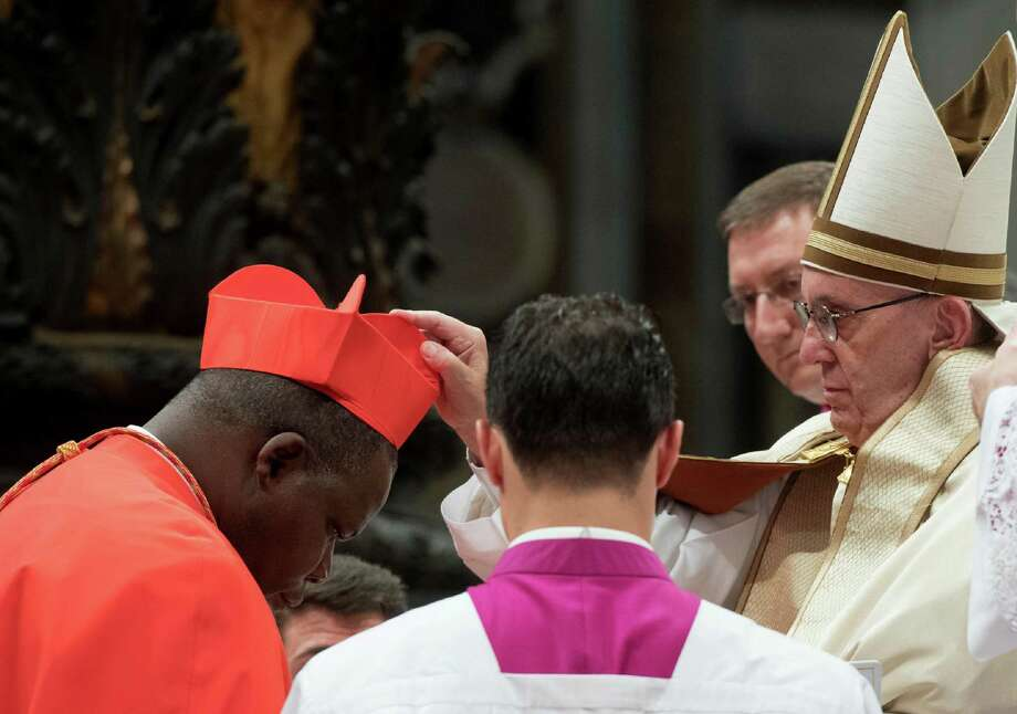 New Cardinal Dieudonne Nzapalainga, Archbishop of Bangui, Central African Republic, receives the red three-cornered biretta hat during a consistory inside the St. Peter's Basilica at the Vatican, Saturday, Nov. 19, 2016. In the ceremony to formally give the Catholic church 17 new cardinals, Francis lamented how immigrants, refugees, and those from different races or faiths are increasingly seen as enemies. (L'Osservatore Romano/pool photo via AP) Photo: L'Osservatore Romano, POOL / ap