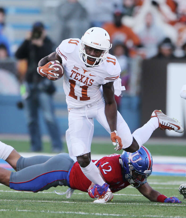 Texas wide reciever Jacorey Warrick (11) is tripped up by Kansas safety Bryce Torneden (12) during the first half at Memorial Stadium in Lawrence, Kan., on Saturday, Nov. 19, 2016. Photo: Deborah Cannon, TNS / Austin American-Statesman