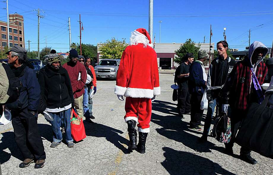 """Louis Gould, once homeless himself, has rebuilt his life with the help of Direct Hope, which provided meals, blankets, books and clothes to homeless people on Saturday in downtown Houston. Gould, 6-foot-6 and lean, says playing Santa is """"one of the most enjoyable things in my life."""" Photo: James Nielsen, Staff / © 2016  Houston Chronicle"""