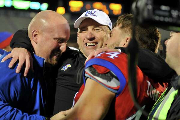 LAWRENCE, KS - NOVEMBER 19: David Beaty head coach of the Kansas Jayhawks celebrates with a fan and fullback Michael Zunica #44 after they beat the Texas Longhorns 24-21 in the overtime at Memorial Stadium on November 19, 2016 in Lawrence, Kansas. Kansas won 24-21.