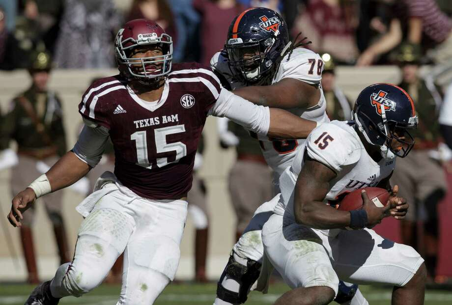 Texas A&M defensive lineman Myles Garrett, left, makes a one-handed sack of UTSA quarterback Jared Johnson Saturday. Garrett finished with 41/2 sacks. Photo: Sam Craft, FRE / AP