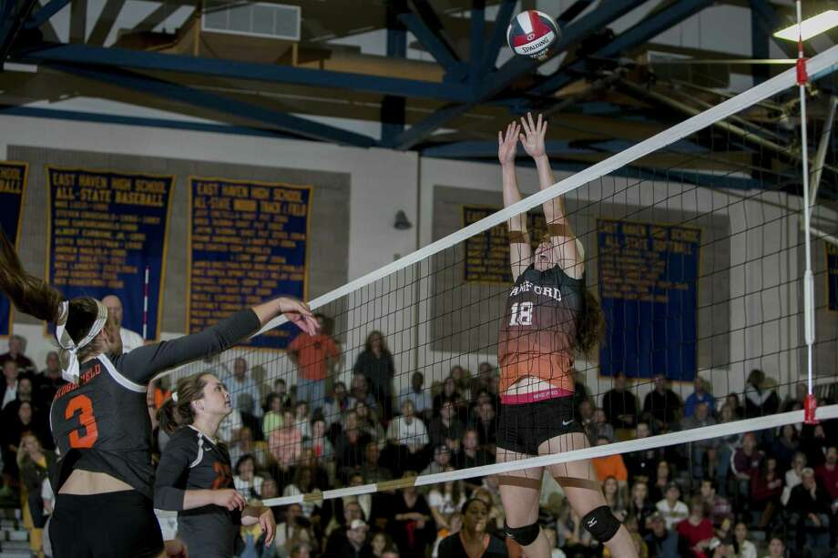 Ridgefield's Caroline Curnal hits the ball past Stamford's Lauren O'Neill in the Class LL girls volleyball final between Ridgefield and Stamford in East Haven on Saturday. Stamford won 3-1. Photo: Johnathon Henninger / For Hearst Connecticut Media / Connecticut Post Freelance