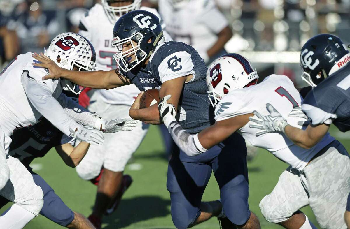 Buttons running back Caleb Salinas is sandwiched in the middle as Central Catholic hosts Dallas Bishop Dunne in the TAPPS Division I second round football playoffs at Benson Stadium on November 19, 2016.