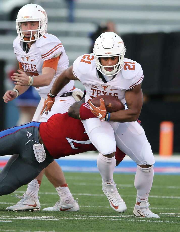 Texas running back Kyle Porter (21) tries to shake off Kansas defensive end Dorance Armstrong (2) during the first half at Memorial Stadium in Lawrence, Kan., on Saturday, Nov. 19, 2016. (Deborah Cannon/Austin American-Statesman/TNS) Photo: Deborah Cannon, MBR / TNS / Austin American-Statesman