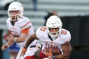 Texas running back Kyle Porter (21) tries to shake off Kansas defensive end Dorance Armstrong (2) during the first half at Memorial Stadium in Lawrence, Kan., on Saturday, Nov. 19, 2016. (Deborah Cannon/Austin American-Statesman/TNS)