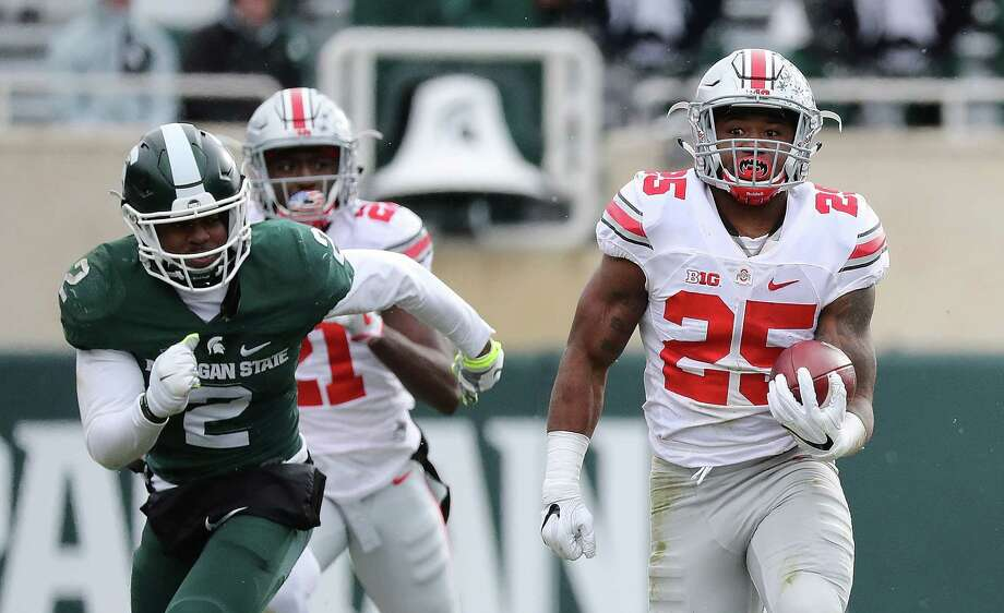EAST LANSING, MI - NOVEMBER 19: Mike Weber #25 of the Ohio State Buckeyes runs for a long run as Montae Nicholson #9 of the Michigan State Spartans makes the stop during the third quarter of the game at Spartan Stadium on November 19, 2016 in East Lansing, Michigan. Ohio State defeated Michigan State 17-16. (Photo by Leon Halip/Getty Images) Photo: Leon Halip, Stringer / 2016 Getty Images
