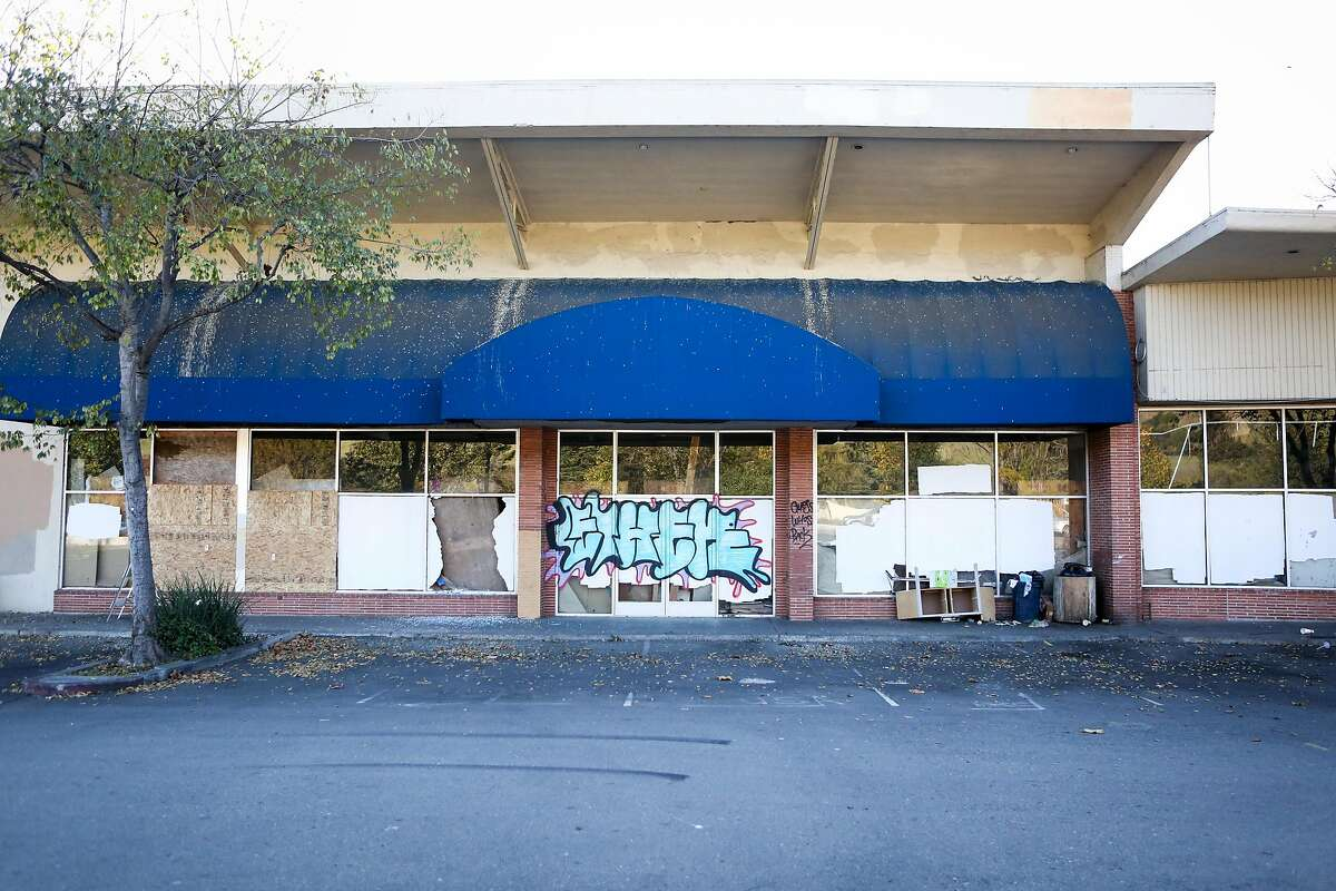 Graffiti and boarded up windows cover most of the decaying strip mall where Curry Corner is located on Thursday, November 19, 2016 in Hayward, Calif.