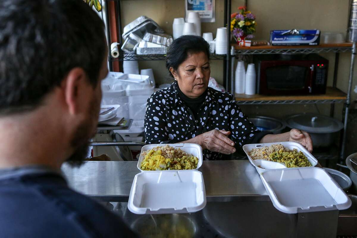 Saras Rao, chef and owner of Curry Corner, prepares take away dishes for a customer Phil Hendricks on Thursday, November 19, 2016 in Hayward, Calif.