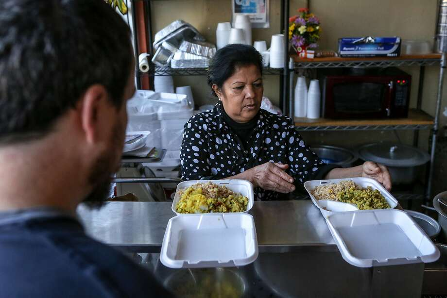 Saras Rao, chef and owner of Curry Corner in Hayward, prepares take-away dishes for customer Phil Hendricks. Photo: Amy Osborne, Special To The Chronicle