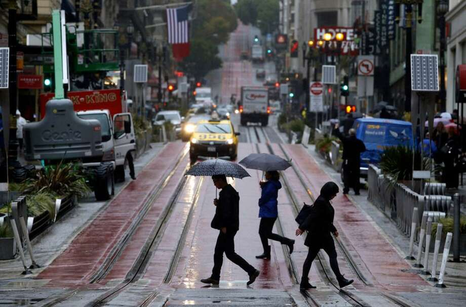 Pedestrians carry umbrellas as they cross Powell Street in San Francisco. Rain showers washed through the Bay Area on Sunday amid what will be a wet week going into the Thanksgiving holiday weekend, forecasters said. Photo: Paul Chinn / San Francisco Chronicle / Paul Chinn / San Francisco Chronicle