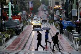 Pedestrians carry umbrellas as they cross Powell Street in San Francisco. Rain showers are expected to continue off and on through the Thanksgiving holiday weekend.