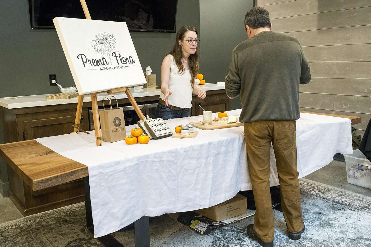 Amanda Jamila talks with a prospective customer while working a booth for the artisan cannabis company Prema Flora during an event at Harvest, a medical marijuana dispensary in the Inner Richmond District, in San Francisco, Calif., on Saturday, November 19, 2016.