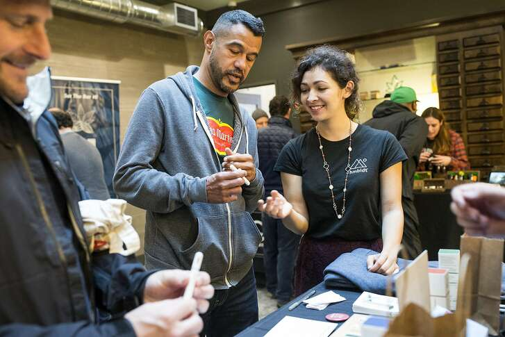Peter Vizcaino and Victor Antonetti try out hmbldt, a health-conscious vaporizer pen, with the help of Rebekah Vega (left to right) during an event at Harvest, a medical marijuana dispensary in the Inner Richmond District, in San Francisco, Calif., on Saturday, November 19, 2016.