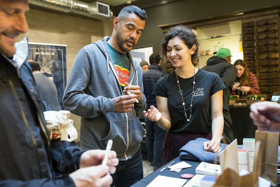 Rebekah Vega assists Peter Vizcaino (left) and Victor Antonetti with a hmbldt vaporizer pen at a November event at medical marijuana dispensary Harvest in S.F. Photo: Laura Morton, Special To The Chronicle