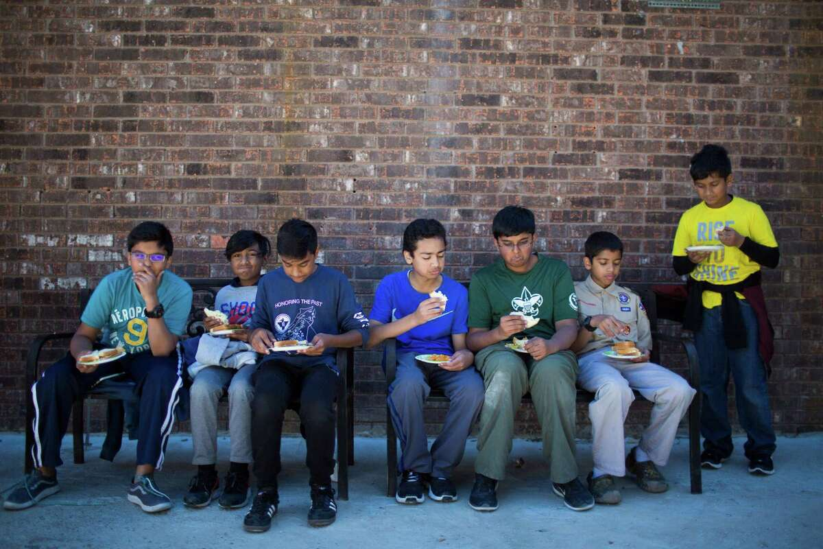 Boys Scouts take a break to lunch after spending the morning building a playground on the back of the Quba Islamic Institute in Houston which had been burned down on early 2015. Sunday, November, 20, 2016.