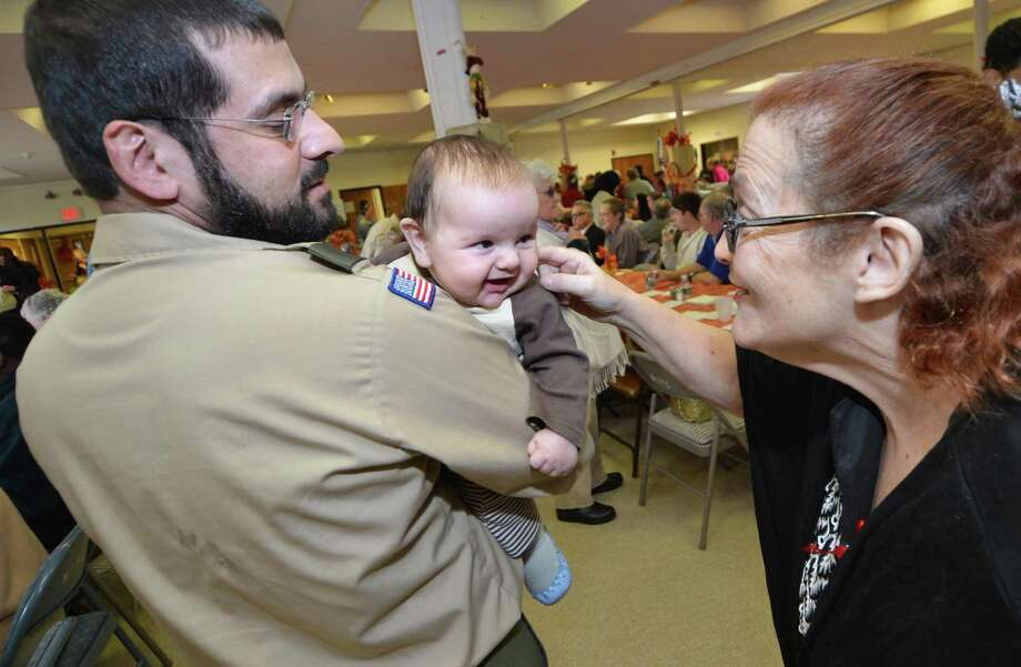 Bassam El-Abid of Boy Scout Troop 19 holds his smiling 3.5-month-old son, Omar, as Gail Kantzan gives him a tickle during the Community Thanksgiving Luncheon at Cornerstone Community Church on Sunday. Turkey and all the trimmings were served up to about 300 people by church members and volunteers. It was the 17th year for the event. Photo: Alex Von Kleydorff / Hearst Connecticut Media / Connecticut Post