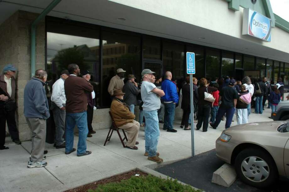 A line of customers wraps around the building outside of  the Cablevision Optimum Store on Main Street, in Bridgeport, Conn. Wednesday, May 19th, 2010. Photo: Ned Gerard / Connecticut Post