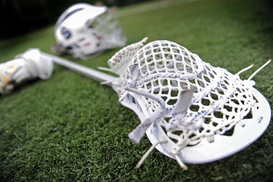 A Staples lacrosse stick and helmet lay on the field before the start of game action against Fairfield Ludlowe Wednesday May 19, 2010 at Ludlowe's Taft Field. Photo: Autumn Driscoll / Connecticut Post