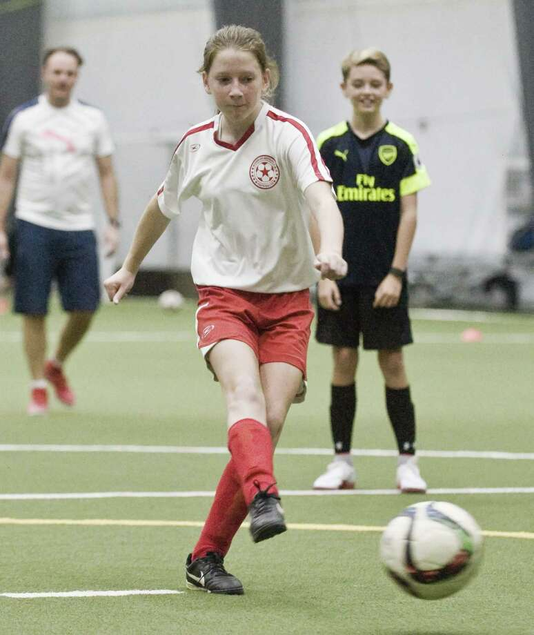 """Kate Greene, a U13 youth soccer player, boots the ball at the Futbol Friends International third annual """"six2six"""" soccer marathon at the Newtown Youth Academy. Sunday, Nov. 20, 2016 Photo: Scott Mullin / For Hearst Connecticut Media / The News-Times Freelance"""