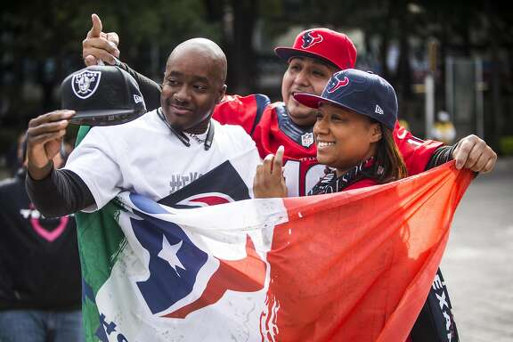 LaTasha Williams, right, covers up Derrick Holmes' Oakland Raiders gear during a gathering of the Traveling Texans at the Angel de la Independencia monument on Sunday, Nov. 20, 2016, in Mexico City. ( Brett Coomer / Houston Chronicle )