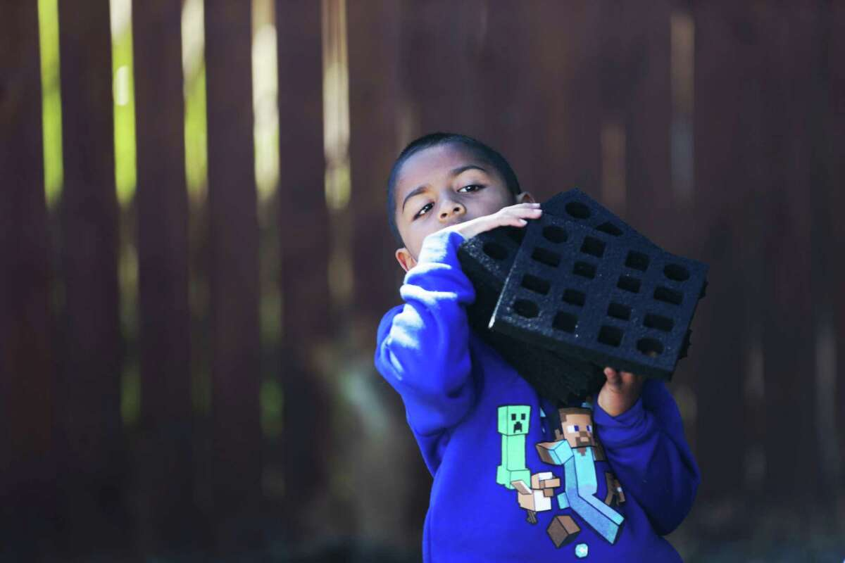 Ahmad Islam, 6, carries soft rubber tiles trying to help his brother finish his Eagle Scout project on Sunday.