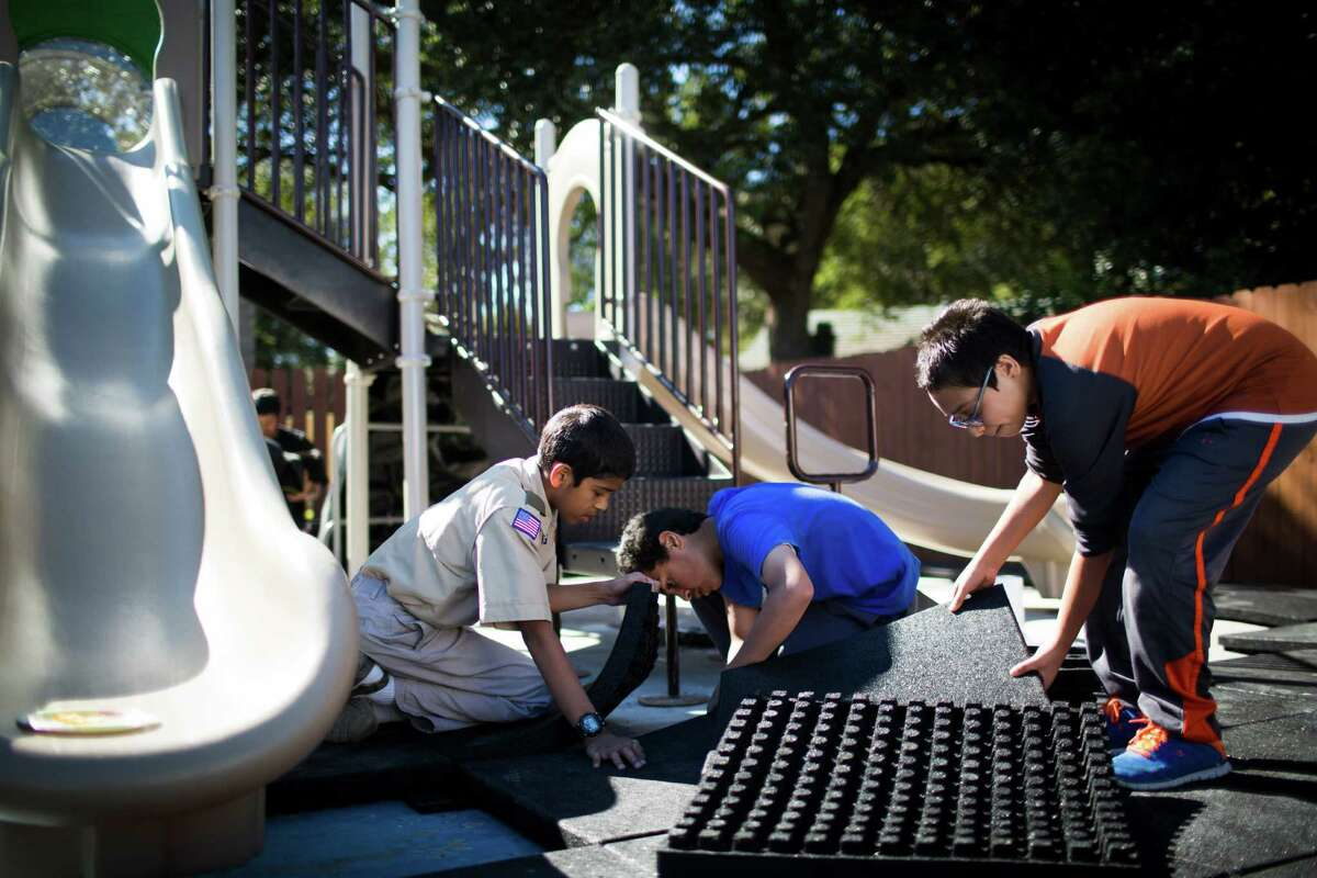 """From left, Ibrahim Islam, 13, Shaheer Siddiqui, 12, and Moazzam Rehan, 12, install rubber tiles as part of the process of building a playground on the back of the Quba Islamic Institute, which had been burned down last February. """"It's even better than before,"""" said Ibrahim, who led the project as part of his Eagle Scout requirement."""