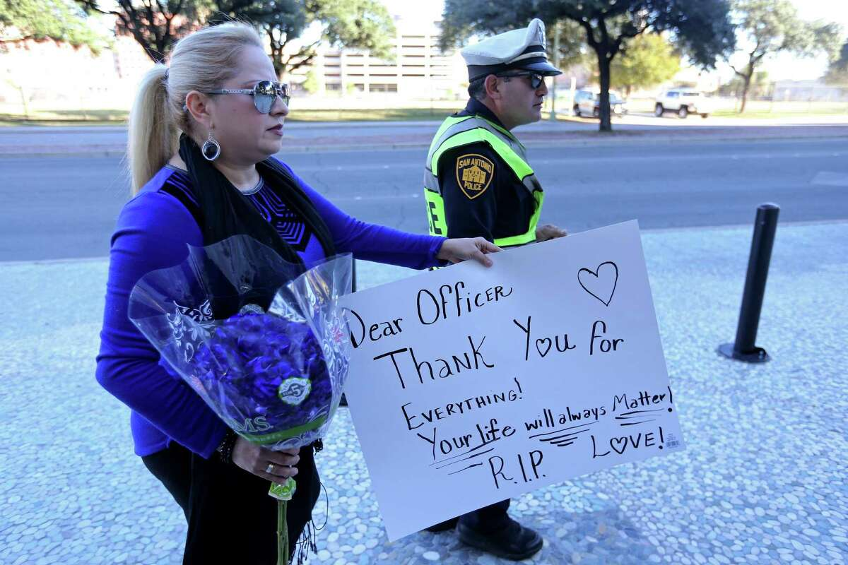 Lucy Aldaba brings flowers and a sign to San Antonio Police Department headquarters after SAPD Det. Benjamin Marconi was shot and killed while performing a routine traffic stop Sunday Nov. 20, 2016.