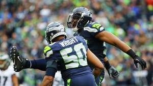 Seahawks linebacker Bobby Wagner (behind) and K.J. Wright celebrate Wagner's sack of Eagles quarterback Carson Wentz in the first quarter of the Seahawks game against the Philadelphia Eagles, Sunday, Nov. 20, 2016 at CenturyLink Field.