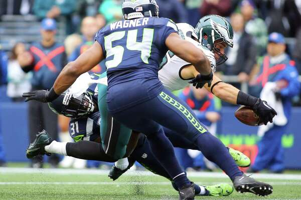 Eagles tight end Zach Ertz stretches out over the goal line past Seahawks linebacker Bobby Wagner and Seahawks safety Kam Chancellor to score a touch down in the second quarter of the Seahawks game against the Philadelphia Eagles, Sunday, Nov. 20, 2016 at CenturyLink Field.