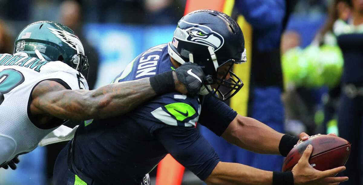 Seahawks quarterback Russell Wilson, defended by Eagles linebacker Nigel Bradham, runs the ball into the end zone after making a reception in the third quarter of the Seahawks game against the Philadelphia Eagles, Sunday, Nov. 20, 2016 at CenturyLink Field.