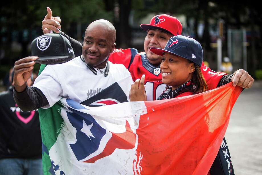 LaTasha Williams, right, covers up Derrick Holmes' Oakland Raiders gear during a gathering of the Traveling Texans in Mexico City. The NFL has what it characterizes as almost 10 million hard-core fans in Mexico. Photo: Brett Coomer, Staff / © 2016 Houston Chronicle