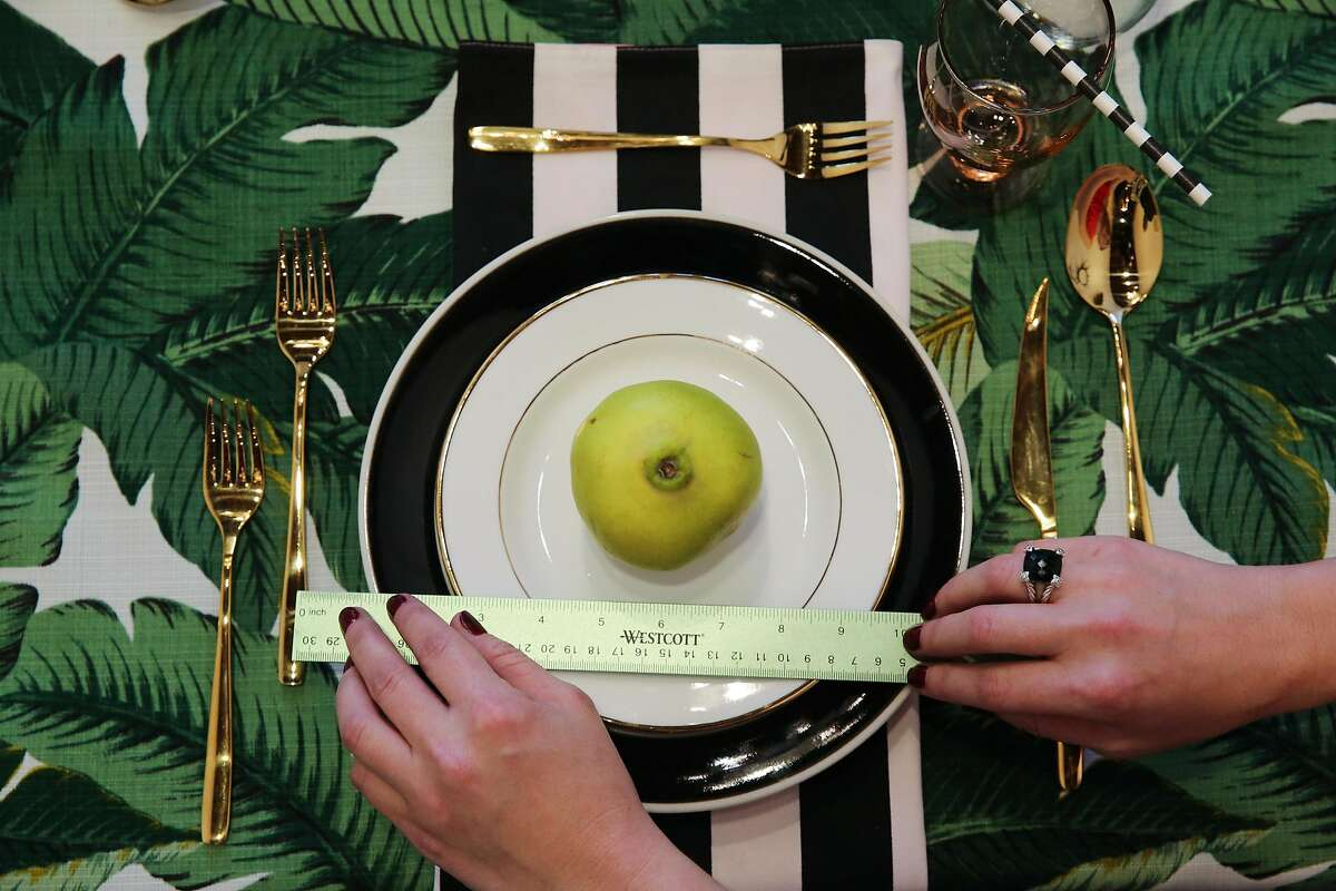 """Owner Liz Curtis measures a plate while she puts final touches on, """"The Monroe"""" table setting, at Table and Teaspoon, in San Francisco, California, on Wednesday, Nov. 16, 2016."""