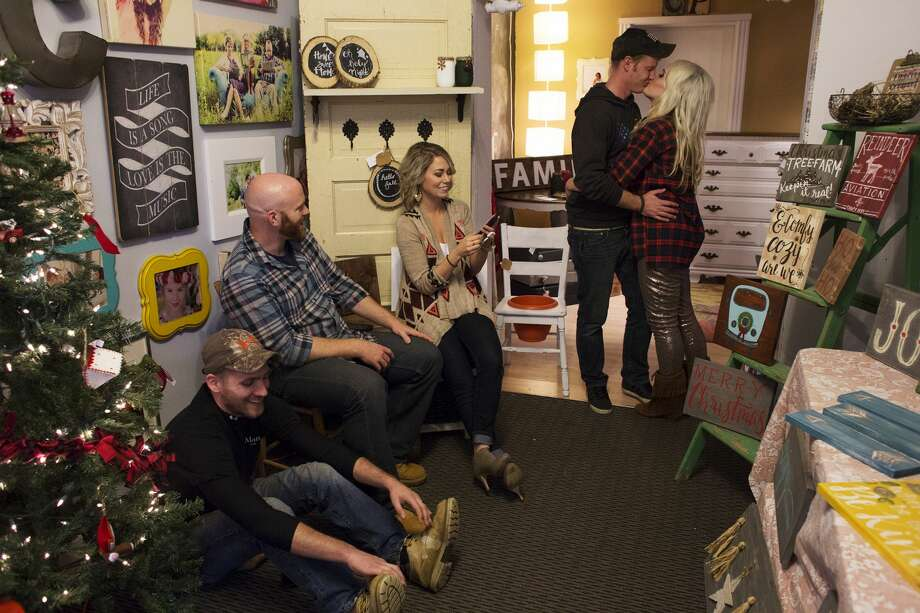 From Left, Matt Koehler, of Auburn, Kevin Wegener, of Midland, Heather Koehler, of Auburn, and Reclaimed Revival, laugh while Stephen and Lacy Robel, of Midland, and Dirtroad Gypsy, share a kiss during the Captured Goes Vintage, a small-business bazaar at the Ashman Collective building on Saturday. Photo: THEOPHIL SYSLO | For The Daily News