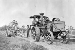 George Kent, one-time mayor of Coleman, is shown operating his steam engine threshing machine. Being pulled is a road grader, usually  horse drawn, but when this picture was snapped the going was too rough for horses. The children didn't usually ride on the grader; they just climbed aboard to have their picture taken. Kent owned one of the first cars in Coleman. His father was a first settler who cleared some of the land north of that community.