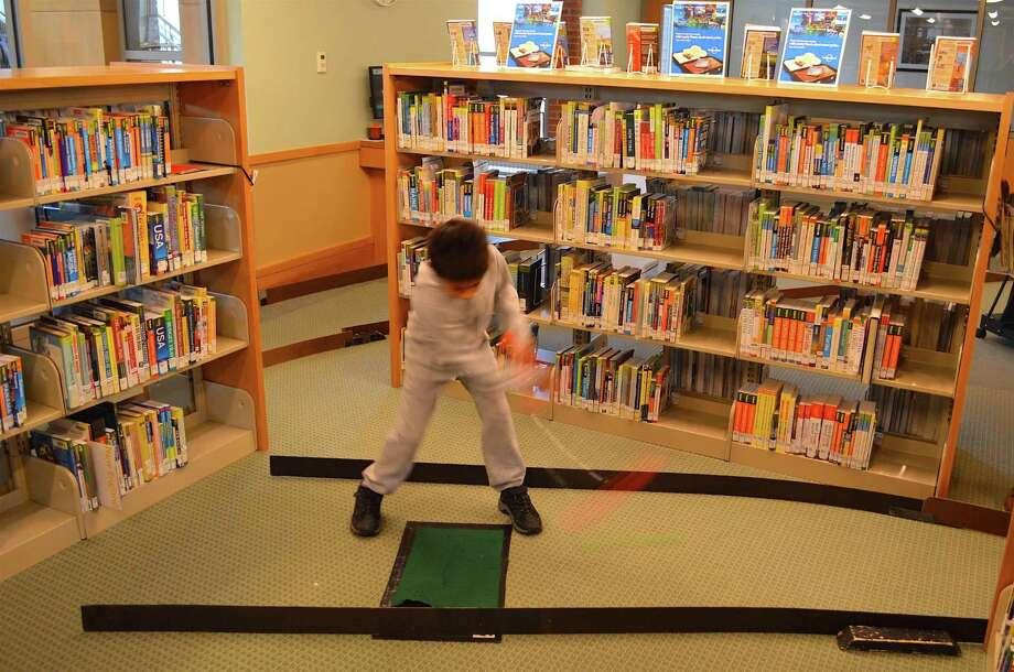 Arjun Sukhrani, 6, of Darien, sent the ball sailing at Darien Library's annual Mini Golf event, Saturday, Nov. 19, 2016, in Darien, Conn. Photo: Jarret Liotta / For Hearst Connecticut Media / Darien News Freelance