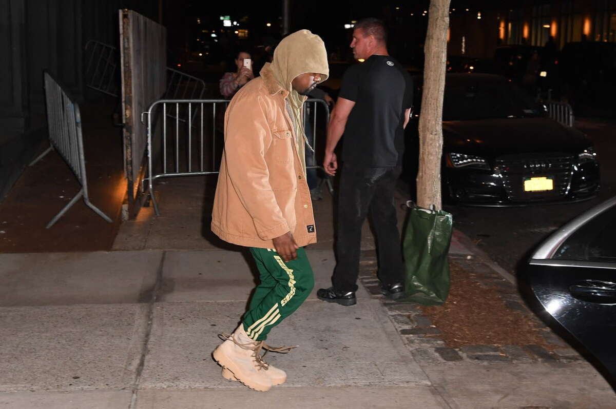"""Kanye West leaves his apartment in New York on October 4, 2016. Kim Kardashian freed herself and raised the alarm after being tied up and robbed at gunpoint in Paris of USD 10 million in jewels in Paris, police sources said. The mother of two and wife of rap superstar Kanye West flew home to the US on Monday after being questioned by police over the incident, which a spokeswoman said had left her """"badly shaken"""". / AFP PHOTO / Angela WEISSANGELA WEISS/AFP/Getty Images"""