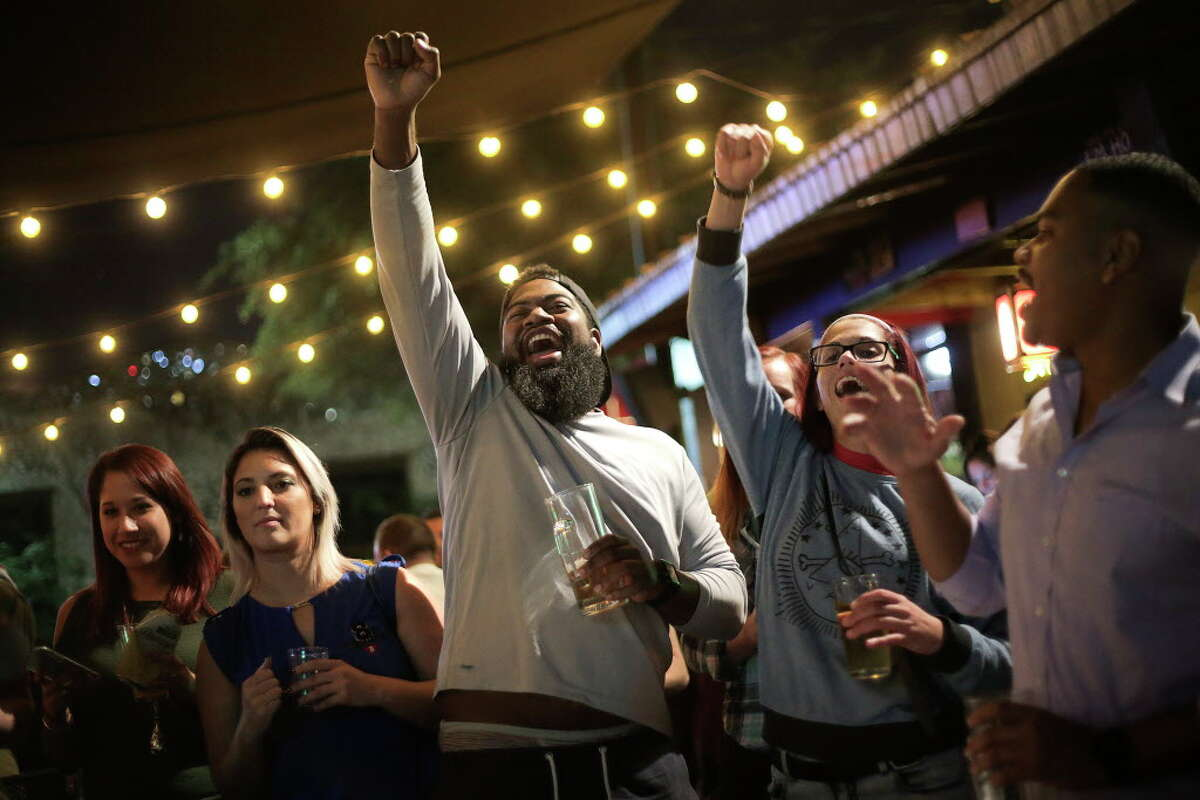 Glenn Lewis, center, and Christina Mevs celebrate a win during the Hermit crab races at Little Woodrows in Eado on Tuesday, Nov. 15, 2016, in Houston.